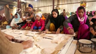 AMRITSAR, INDIA - 1 MARCH 2015: Group of people preparing dough at public kitchen in Amritsar.