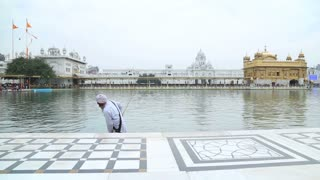AMRITSAR, INDIA - 1 MARCH 2015: Indian man cleaning pool water in front of the Golden temple in Amritsar.
