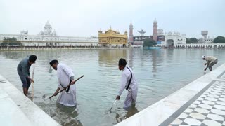 AMRITSAR, INDIA - 1 MARCH 2015: Indian men cleaning pool water in front of the Golden temple in Amritsar.