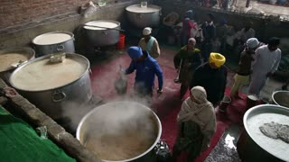 AMRITSAR, INDIA - 1 MARCH 2015: Local people preparing food in large kettles in public kitchen in Amritsar.
