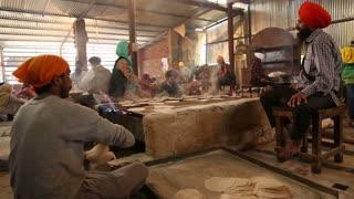 AMRITSAR, INDIA - 1 MARCH 2015: Men preparing Indian bread at public kitchen in Amritsar.
