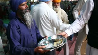 AMRITSAR, INDIA - 1 MARCH 2015: Portrait of Indian man passing down empty plates in public kitchen in Amritsar.