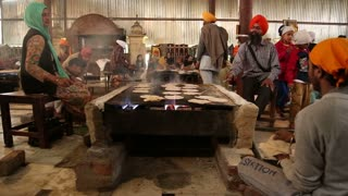 AMRITSAR, INDIA - 1 MARCH 2015: Workers preparing Indian bread at public kitchen in Amritsar.