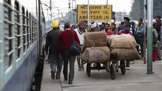 AMRITSAR, INDIA - 2 MARCH 2015: Group of men carrying load passing by people at the train station in Amritsar.