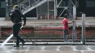 AMRITSAR, INDIA - 2 MARCH 2015: Man washing the train platform while young man stands on railway behind.