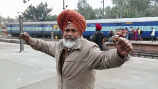 AMRITSAR, INDIA - 2 MARCH 2015: Portrait of man holding his hands widely spread at train station in Amritsar.