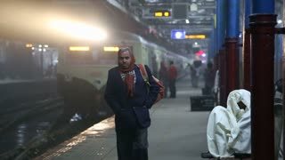 AMRITSAR, INDIA - 2 MARCH 2015: Portrait of man walking down the station while train arrives in background.