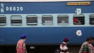 AMRITSAR, INDIA - 2 MARCH 2015: Train arriving at the train station in Amritsar, with people passing by.