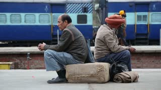 AMRITSAR, INDIA - 2 MARCH 2015: Two men sitting on sack and waiting at train station in Amritsar.