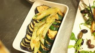 Arranging grilled vegetables on plate