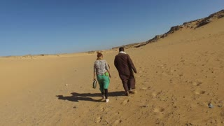 ASWAN, EGYPT - FEBRUARY 7, 2016: Back view of nubian man wearing traditional clothing walking in desert with female tourist.