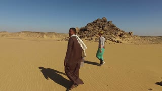 ASWAN, EGYPT - FEBRUARY 7, 2016: Nubian man wearing traditional clothing walking in desert with female tourist.
