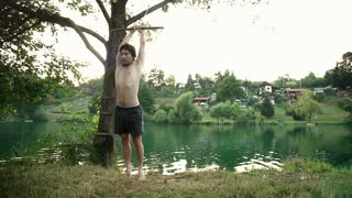 Athletic young man doing backflip off rope swing into river at sunset, graded, in slow motion