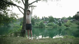 Athletic young man doing backflip off rope swing into river at sunset, slow motion
