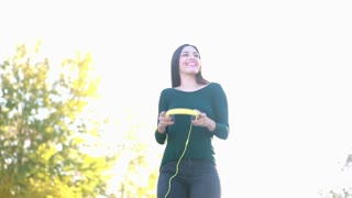 Attractive brunette woman putting on headphones and starts dancing at the park, graded