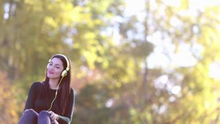 Attractive brunette woman sending kiss to camera while listening to music with headphones at the park, graded