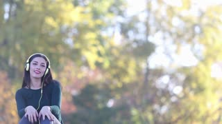 Attractive brunette woman sending kiss to camera while listening to music with headphones at the park, slow motion