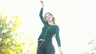 Attractive brunette woman wearing headphones and dancing at the park, graded