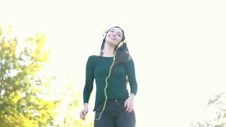 Attractive brunette woman wearing headphones and dancing at the park, sending kiss to camera, slow motion, graded