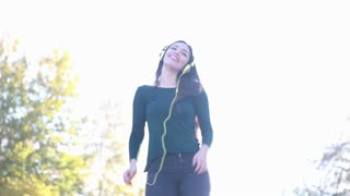Attractive brunette woman wearing headphones and dancing at the park, sending kiss to camera, slow motion
