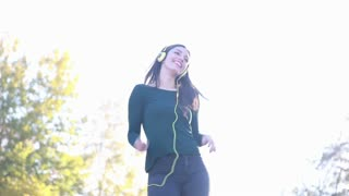 Attractive brunette woman wearing headphones and dancing at the park, sending kiss to camera
