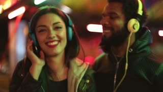 Attractive man and woman dancing to the rhythm of music with headphones