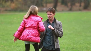Attractive young dad playing with daughter in park, slow motion