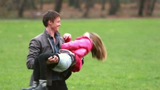 Attractive young dad playing with daughter in park