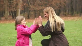 Attractive young mother and her cute daughter playing clapping game