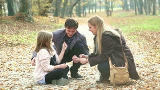 Attractive young parents having fun with cute daughter playing games in the park, graded