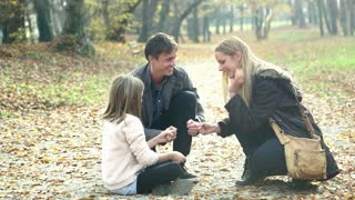 Attractive young parents having fun with cute daughter playing games in the park, slow motion, graded