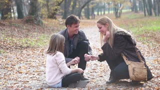 Attractive young parents having fun with cute daughter playing games in the park, slow motion