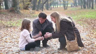 Attractive young parents having fun with cute daughter playing games in the park