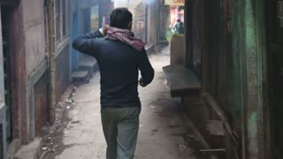 Back view of a man walking down the narrow streets in Varanasi.