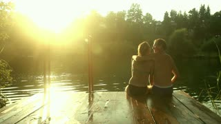 Back view of beautiful couple in love taking selfies and kissing while sitting on the dock by the Mreznica river at sunset, graded