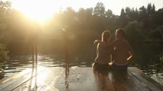 Back view of beautiful couple in love taking selfies and kissing while sitting on the dock by the Mreznica river at sunset