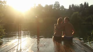 Back view of beautiful romantic couple kissing and hugging while sitting by the Mreznica river at sunset