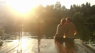 Back view of beautiful romantic couple kissing while sitting by the Mreznica river at sunset, graded
