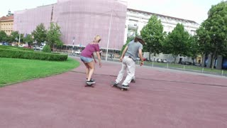 Back view of cool young skateboarders in the city
