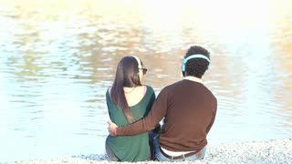 Back view of couple in love sitting by lake and listening to music with headphones, graded