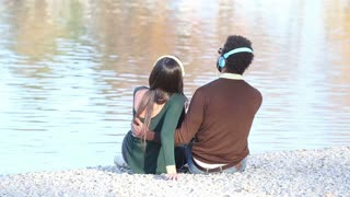 Back view of couple in love sitting by lake and listening to music with headphones