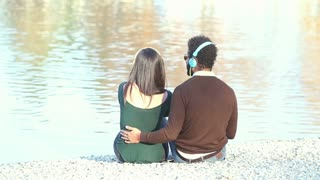 Back view of couple listening to music with headphones, sitting by lake, graded
