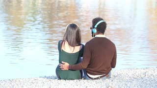 Back view of couple listening to music with headphones, sitting by lake