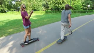 Back view of friends riding on a skateboard