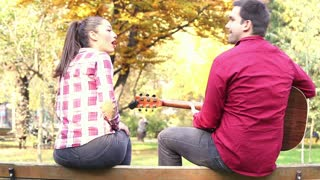 Back view of handsome man playing guitar while beautiful young woman singing, sitting next to him on bench in park, graded