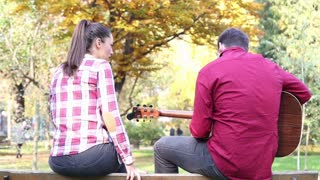 Back view of handsome man playing guitar while beautiful young woman singing, sitting next to him on bench in park