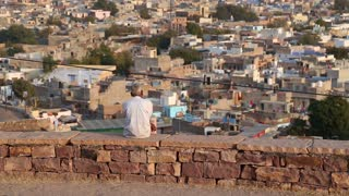 Back view of man sitting on wall watching cityscape.