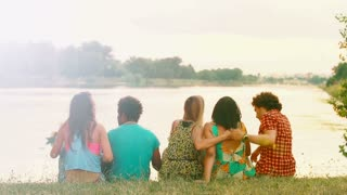 Back view of the group of five young friends sitting on grass and having a good time talking and laughing, graded