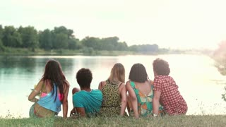 Back view of the group of five young friends sitting on grass, turning around smiling and waving to camera, graded