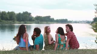Back view of the group of five young friends sitting on grass, turning around smiling and waving to camera
